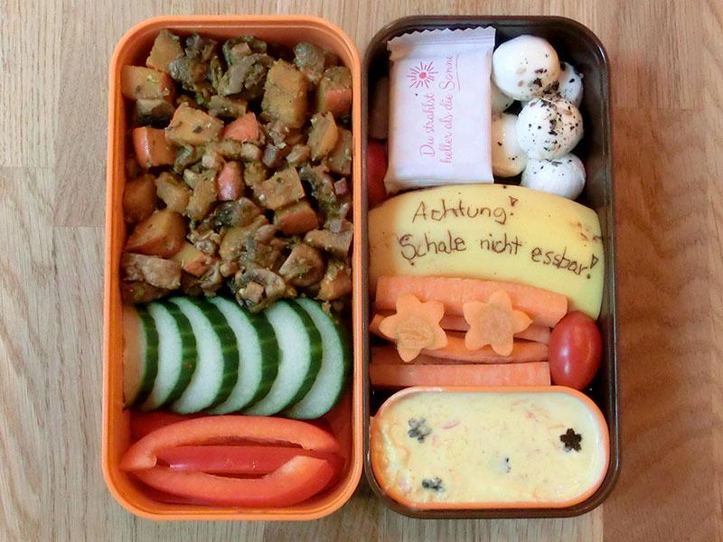 Bento Box gefüllt mit Süßkartoffelpfanne, Gurke, Paprika, Mozarella, Schokolade, Banane, Möhren, Dipp
