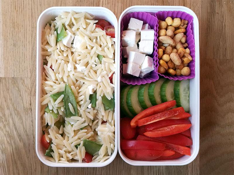 Bento Box gefüllt mit Kritharaki mit Gemüse, Feta, Nüsse, Gurke, Paprika